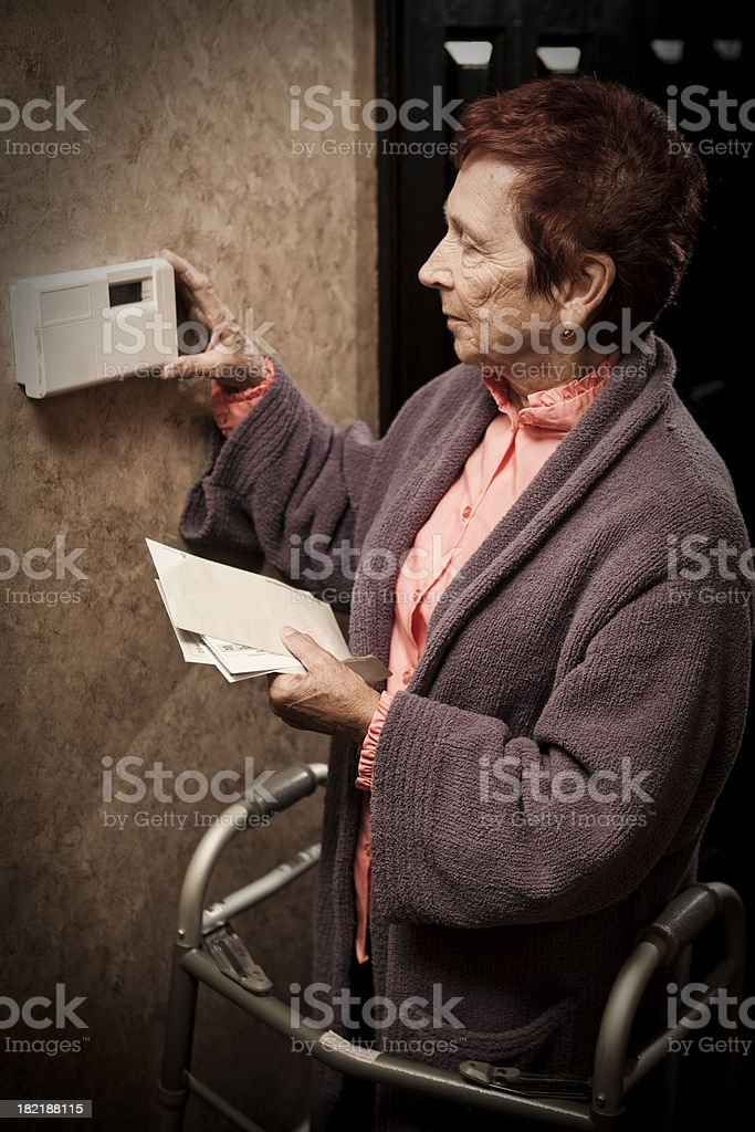 Senior Woman Looking at Bills and Thermostat stock photo
