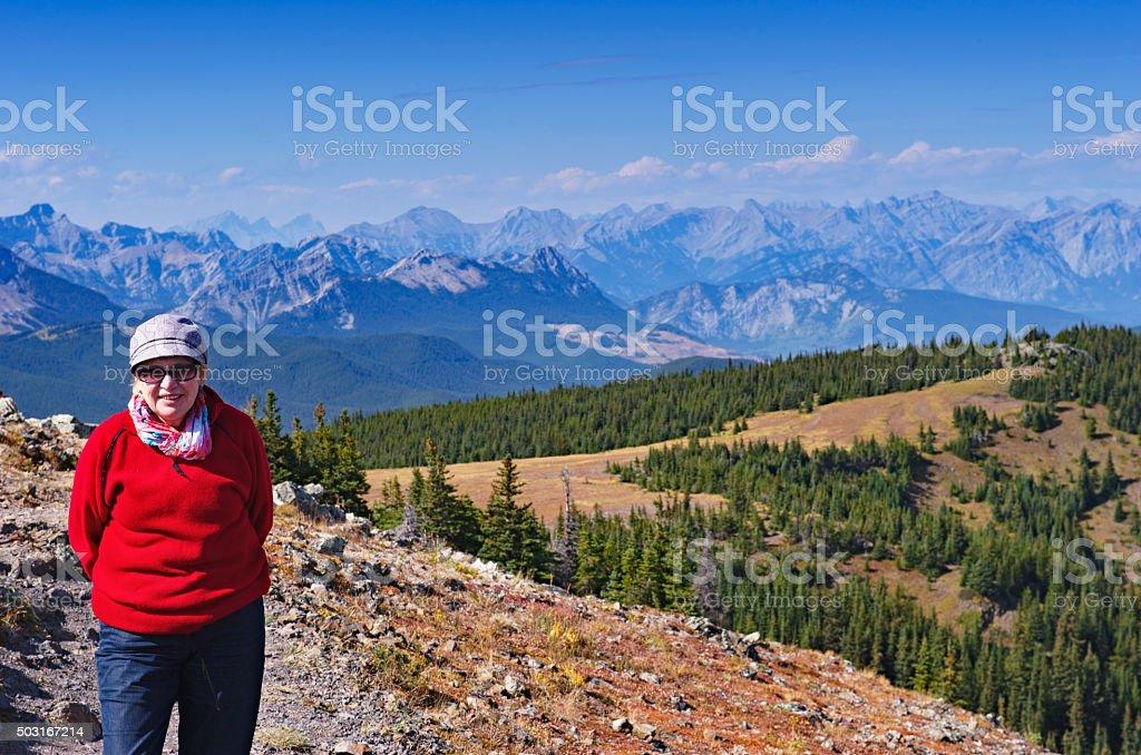 Senior woman looking at camera during hike in Kananaskis stock photo
