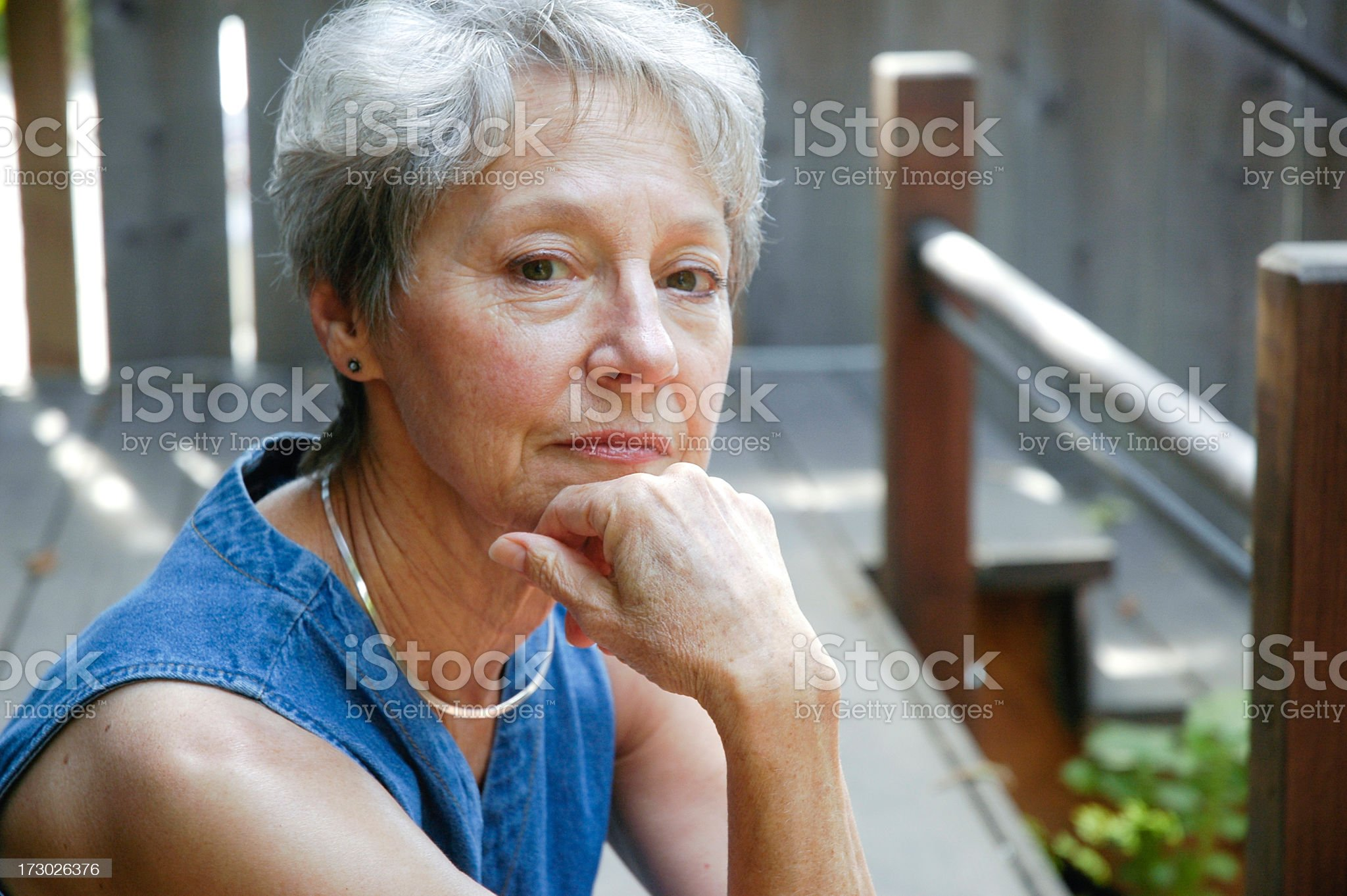 Senior woman looking at camera in a wooden porch royalty-free stock photo