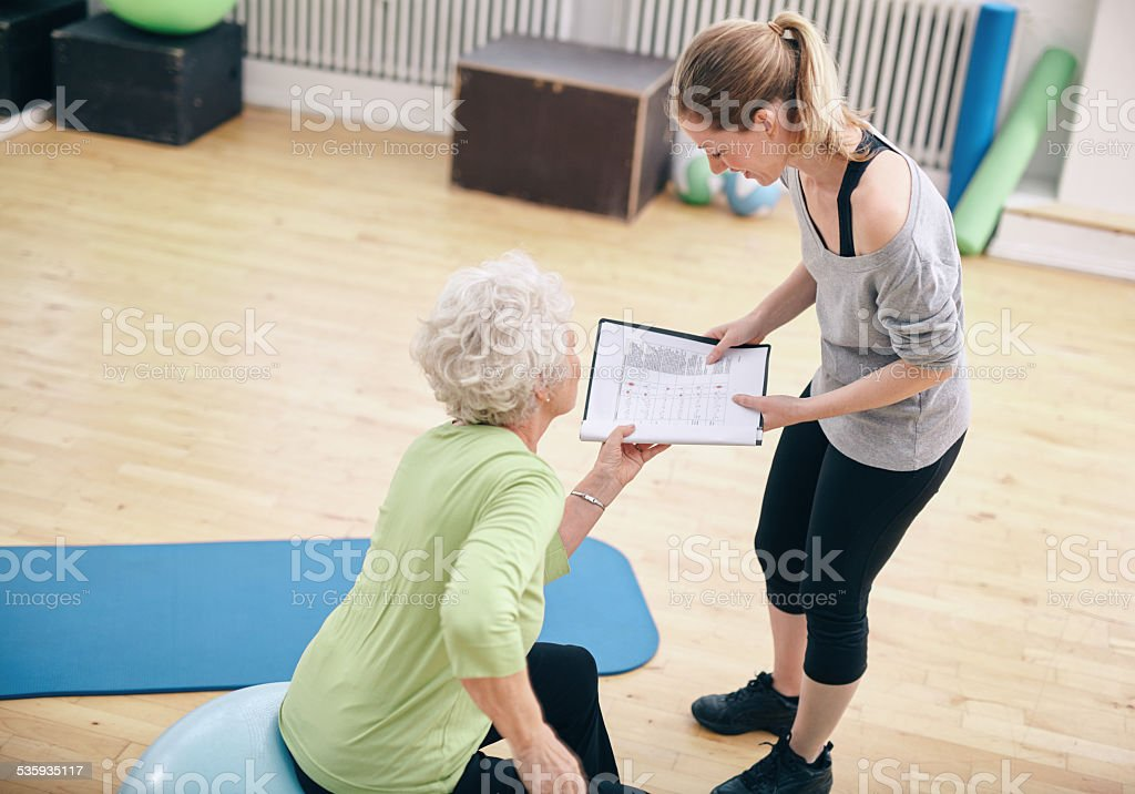 Senior woman looking at exercise plan with personal trainer stock photo