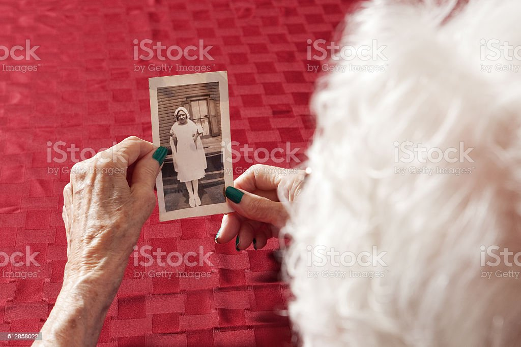 Senior Woman Looking At Her Childhood Photo stock photo