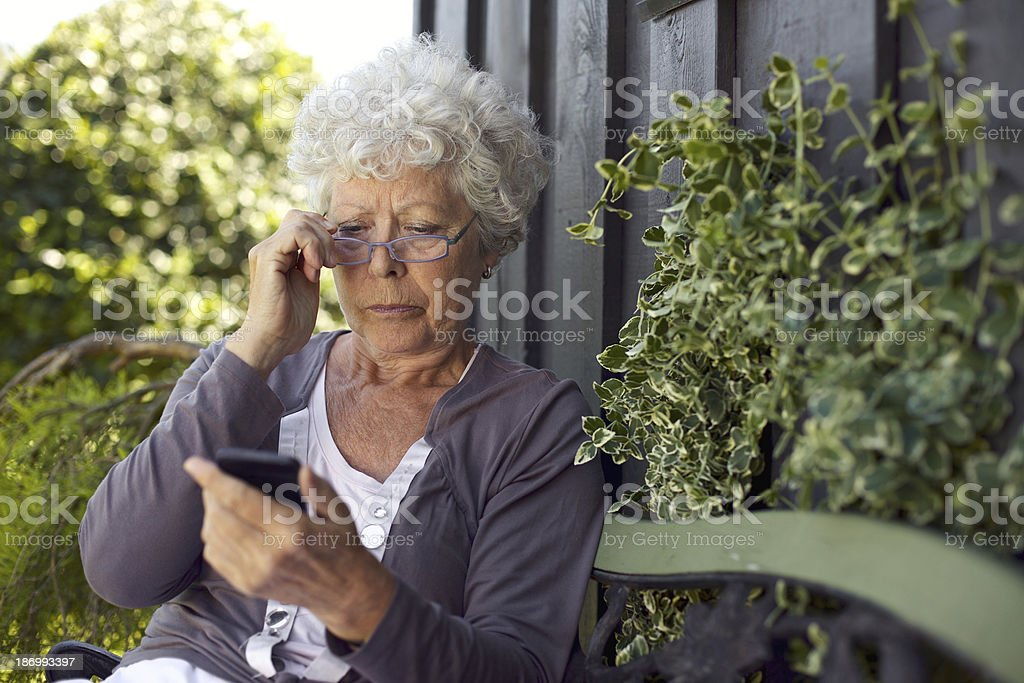 Senior woman looking at mobile phone stock photo