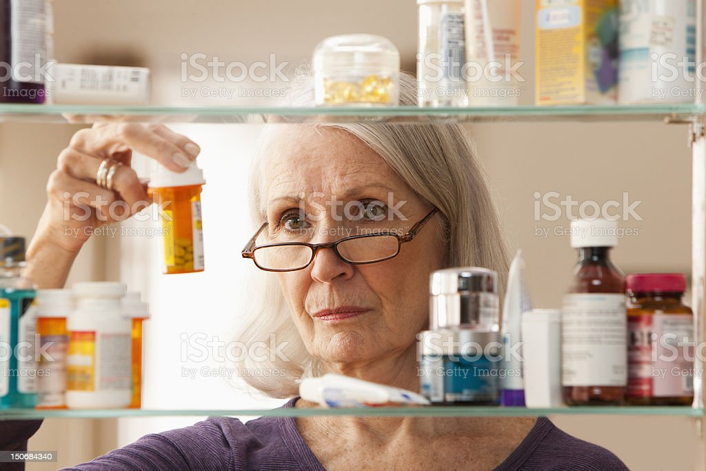 Senior woman looking at prescription bottles stock photo
