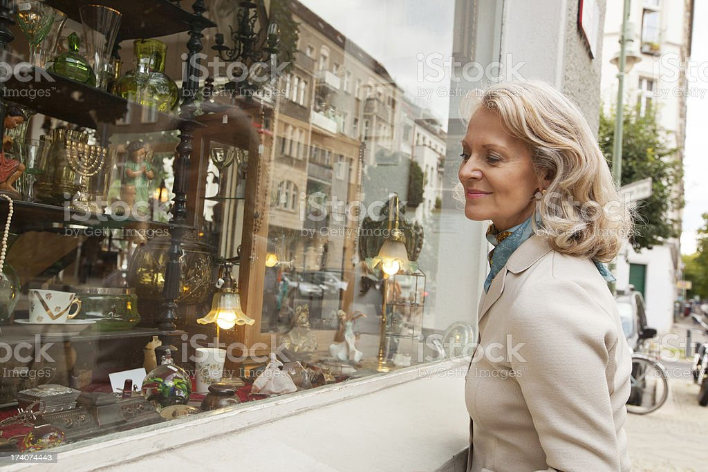Senior woman looking at shopping window stock photo