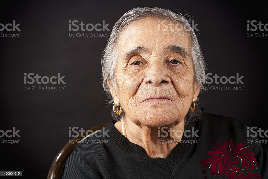A senior woman looking at the camera in a black background stock photo