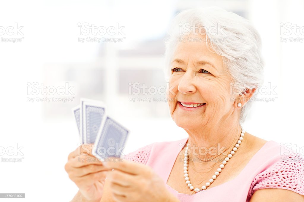 Senior Woman Looking Away While Playing Cards stock photo
