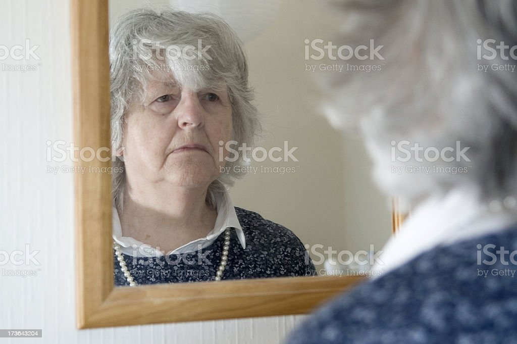 Senior woman looking in mirror royalty-free stock photo