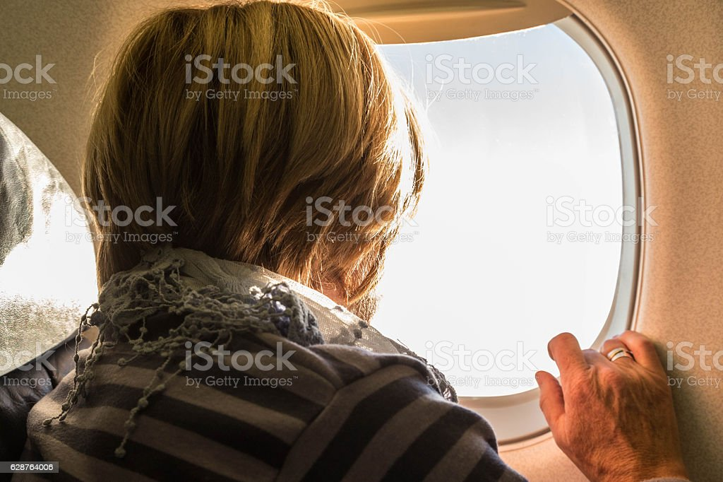 senior woman looking out of plane window stock photo