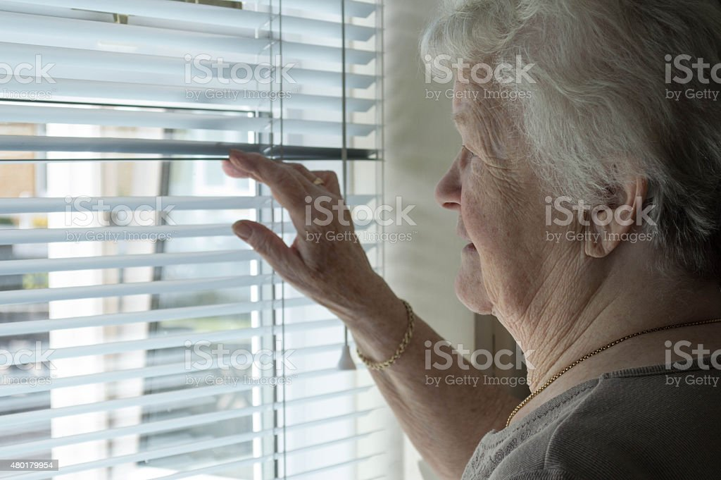Senior woman looking out of the window through blinds stock photo