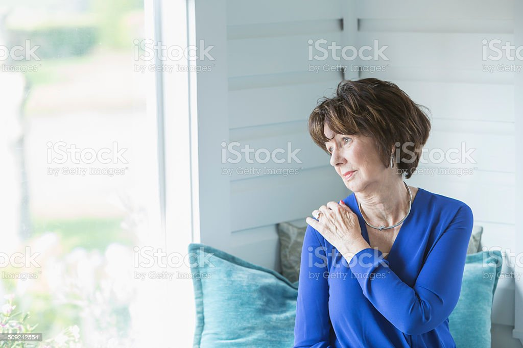 Senior woman looking out window with serious face stock photo