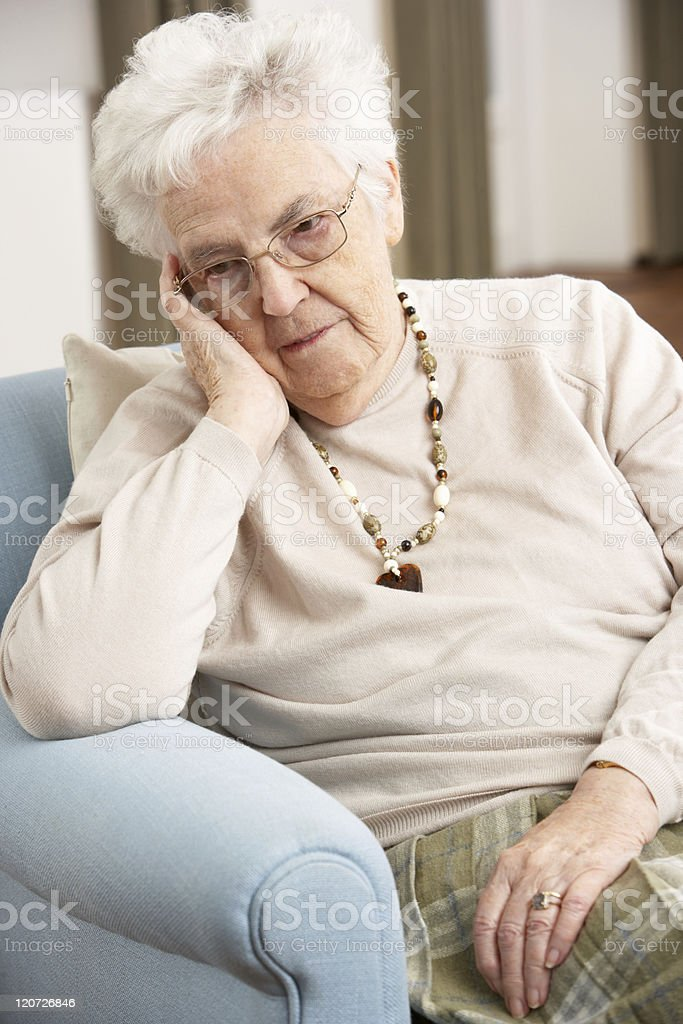 Senior Woman Looking Sad In Chair At Home stock photo