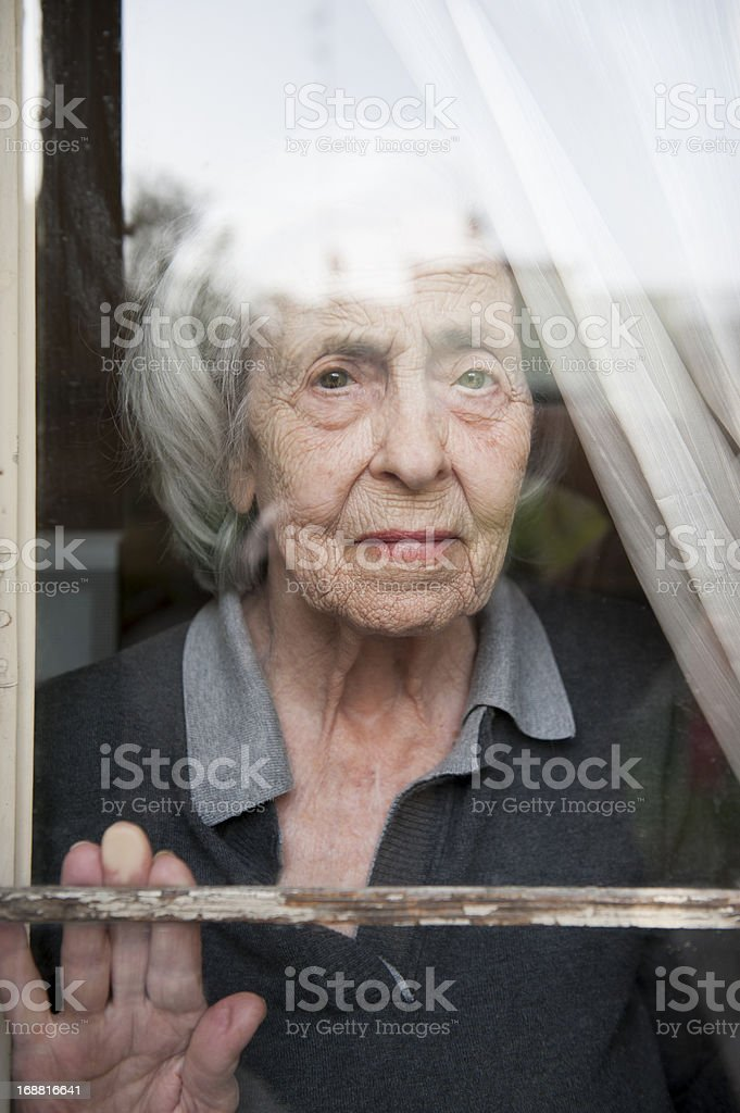 Senior woman looking through a window looking lonely stock photo