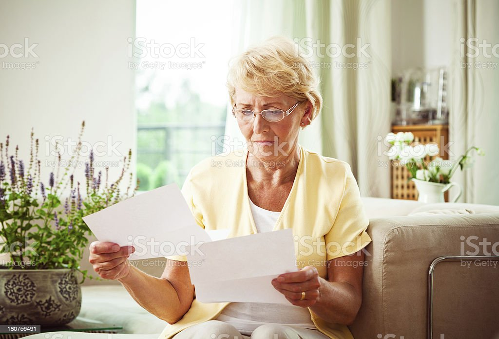 Senior woman looking through bills stock photo