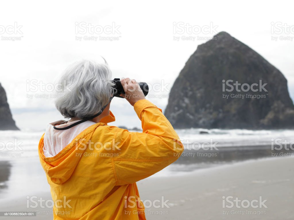 Senior woman looking through binoculars on beach stock photo