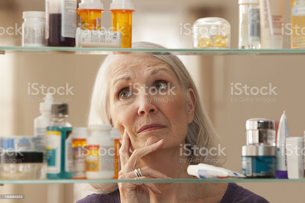 Senior woman looking through medicine cabinet stock photo