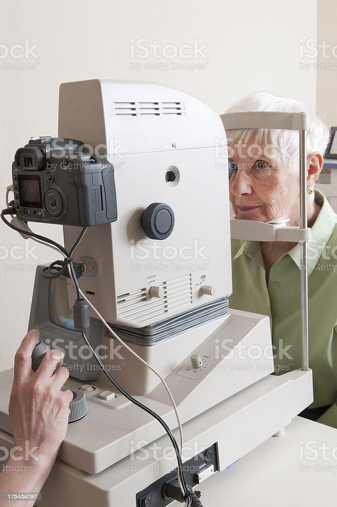 Senior Woman Looking Through Retinal Camera royalty-free stock photo