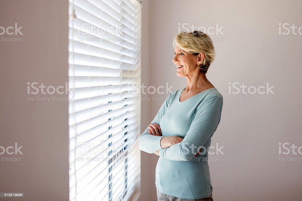 senior woman looking through the blinds stock photo