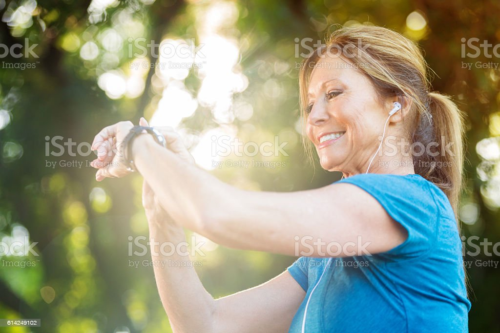 Senior woman looks at fitness tracker after workout stock photo
