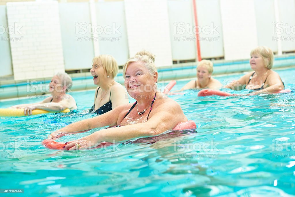 senior woman looks to camera at water aerobics stock photo