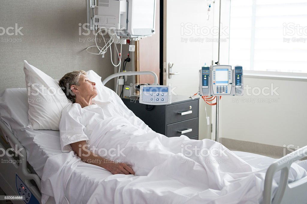 Senior woman lying in hospital bed looking away stock photo