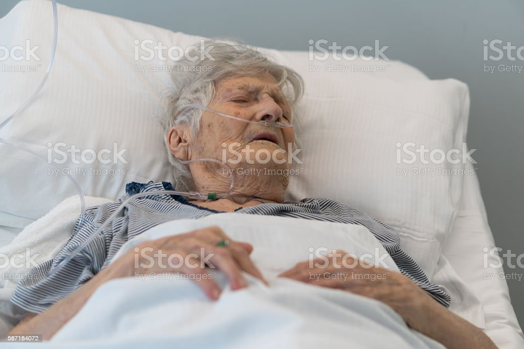 Senior woman lying in hospital bed stock photo