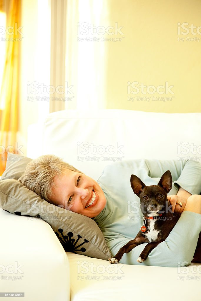 Senior Woman Lying on a sofa with Her Dog royalty-free stock photo