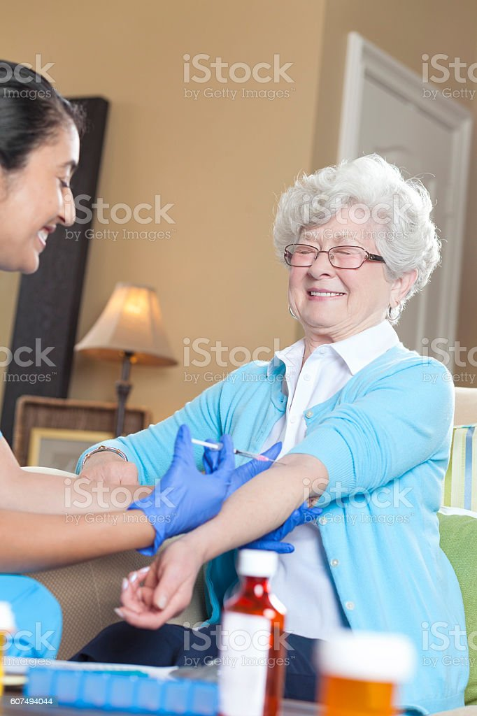 Senior woman makes a face while receiving an injection stock photo