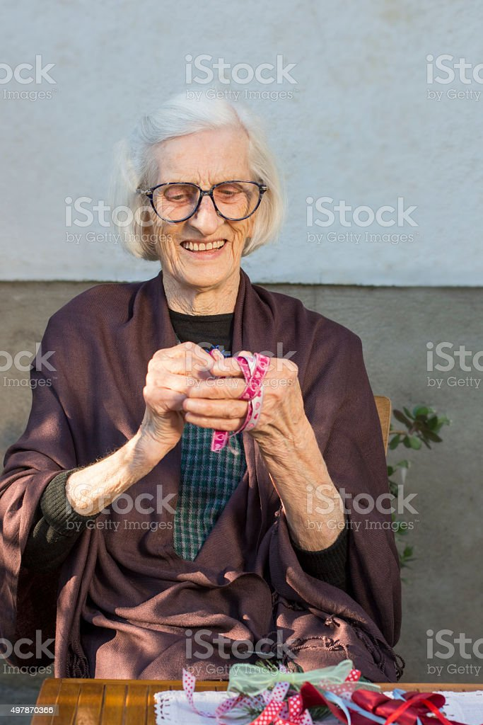 Senior woman making a Christmas decoration in the backyard stock photo