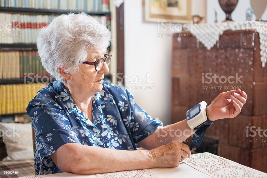 Senior woman measuring her blood pressure at home. stock photo