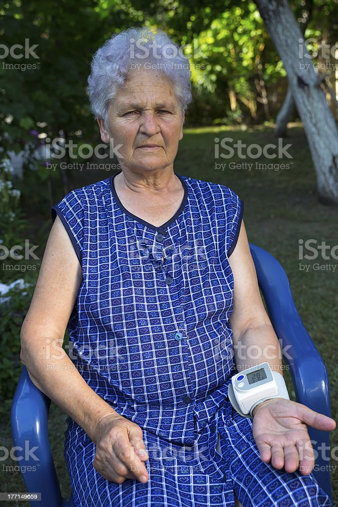 Senior woman measuring her blood pressure royalty-free stock photo