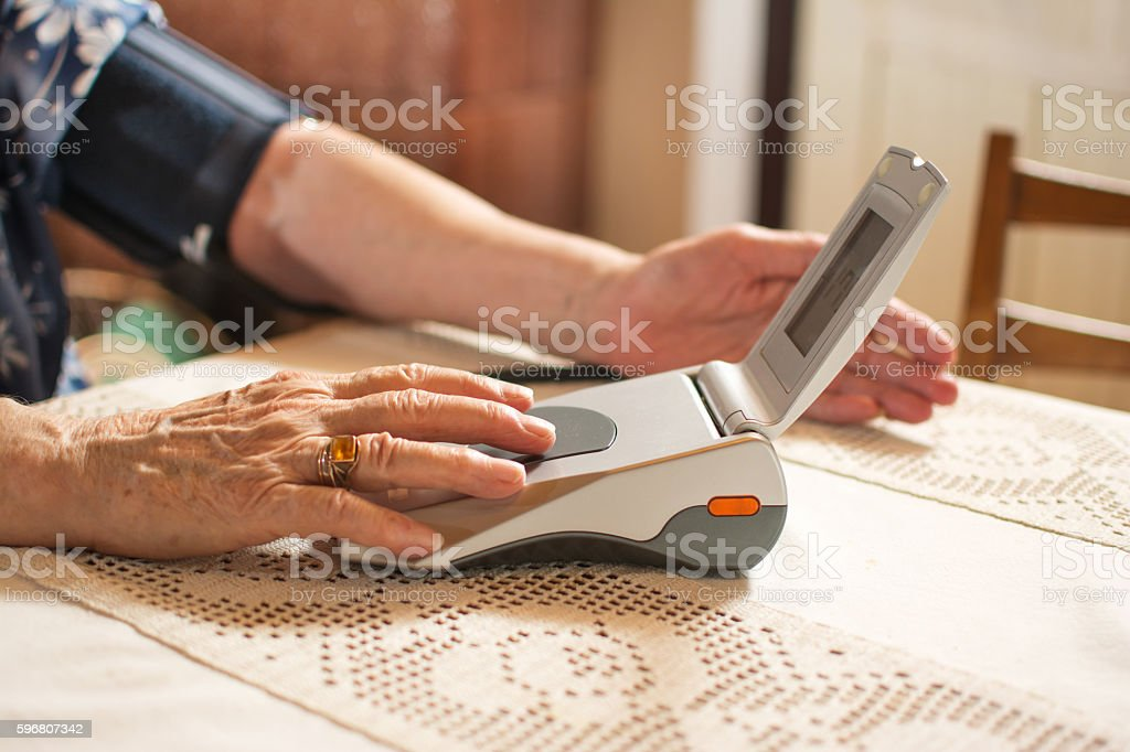 Senior woman measuring her blood pressure. stock photo