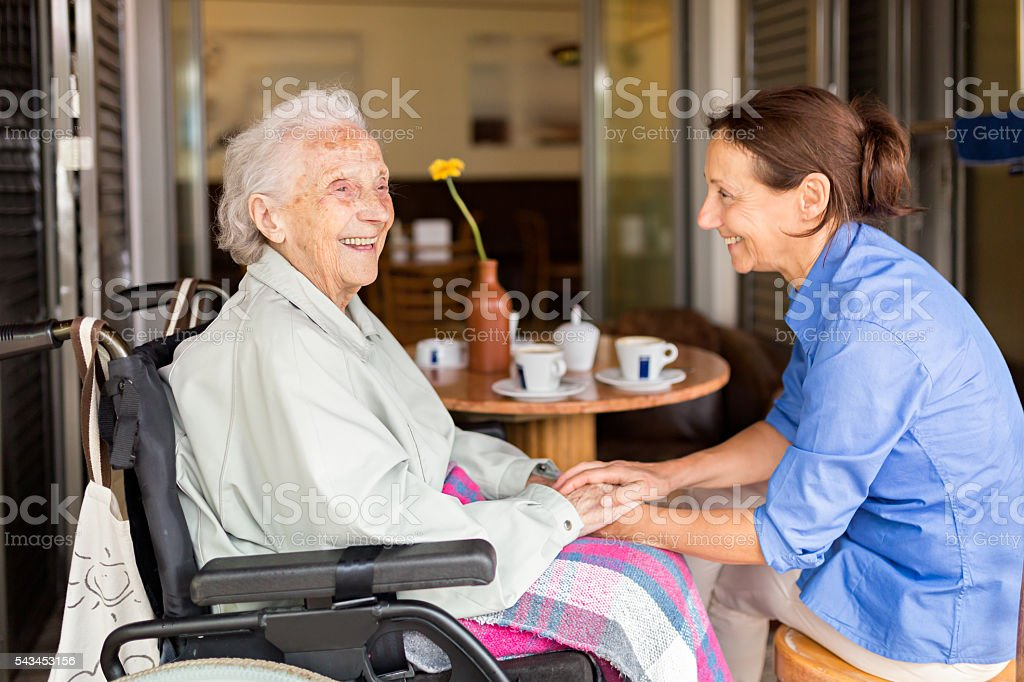 Over 90-year-old woman in a wheelchair and a home caregiver drinking...