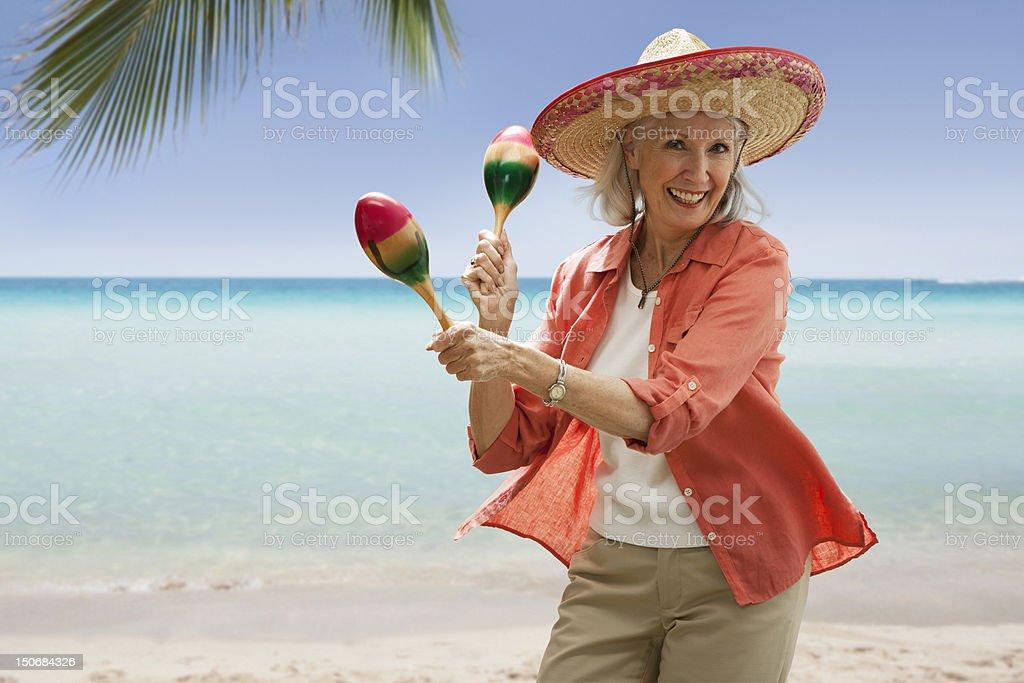 Senior woman on beach with maracas stock photo