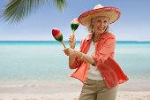 Senior woman on beach with maracas