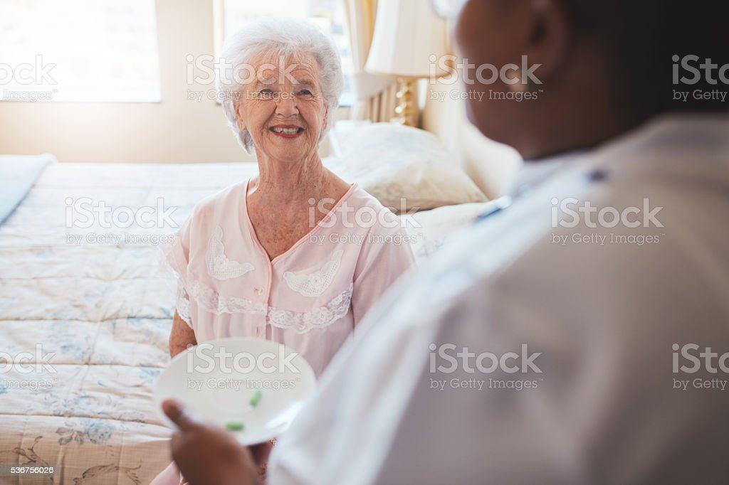 Senior woman on bed with nurse giving medication stock photo