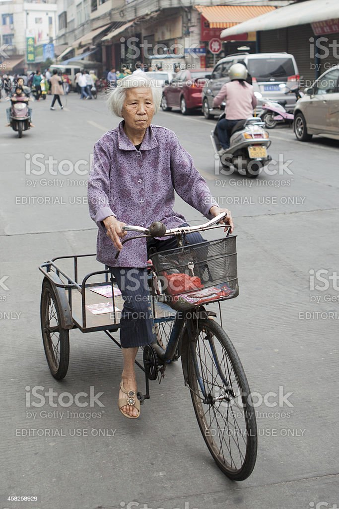 Senior woman on bicycle in China stock photo