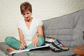 Senior woman on couch, drawing in coloring book