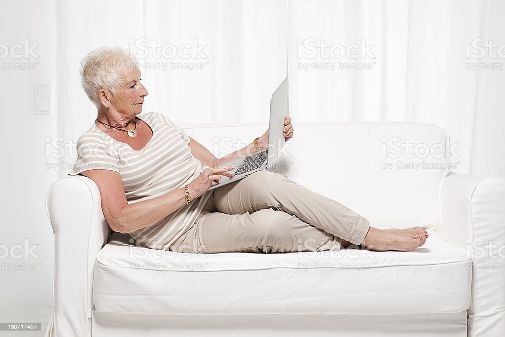 Senior woman on couch with laptop royalty-free stock photo