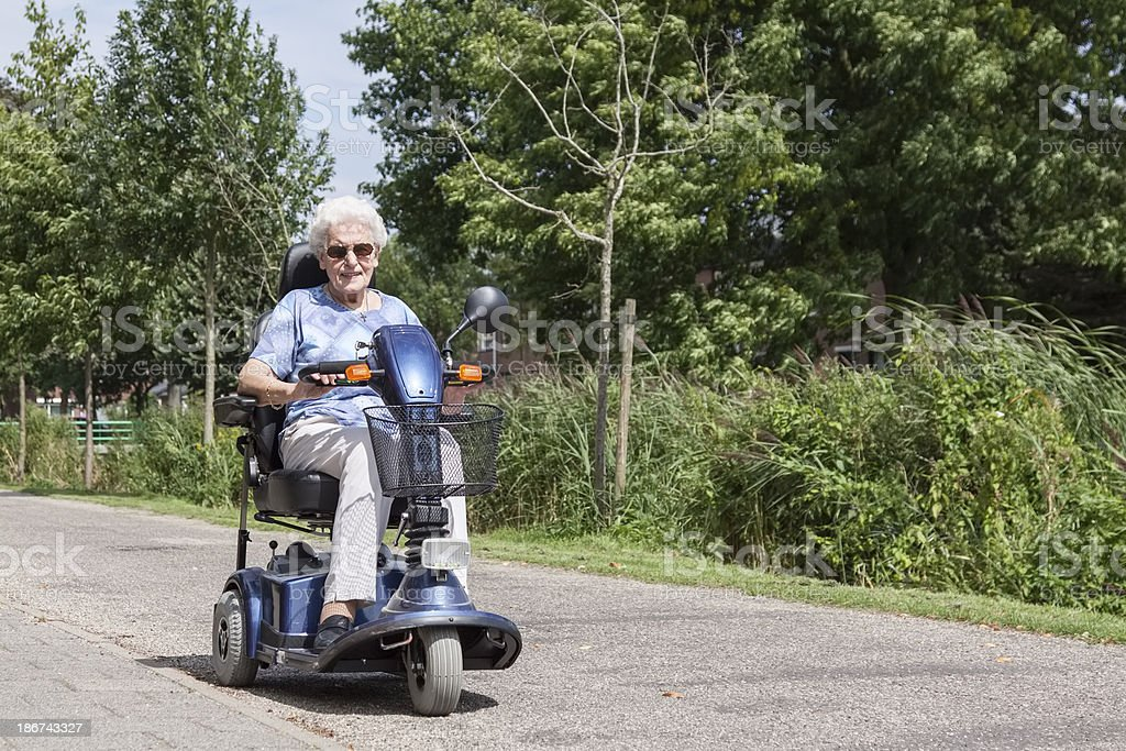 Senior woman on electric scooter stock photo