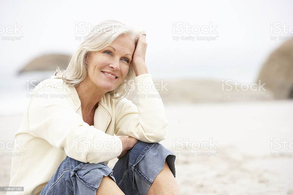 Senior Woman On Holiday Sitting At Winter Beach stock photo