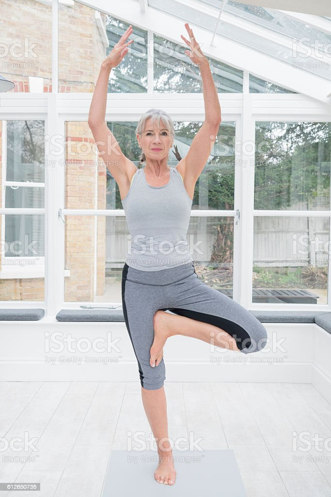 Senior woman on one leg in tree position doing yoga stock photo
