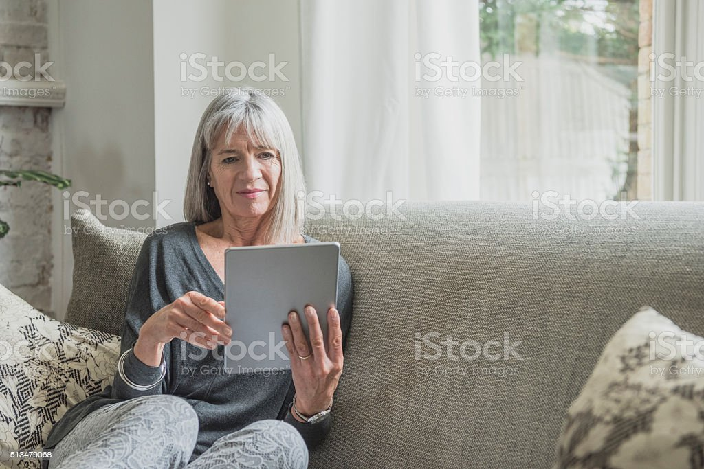 Senior woman on sofa at home using digital tablet stock photo
