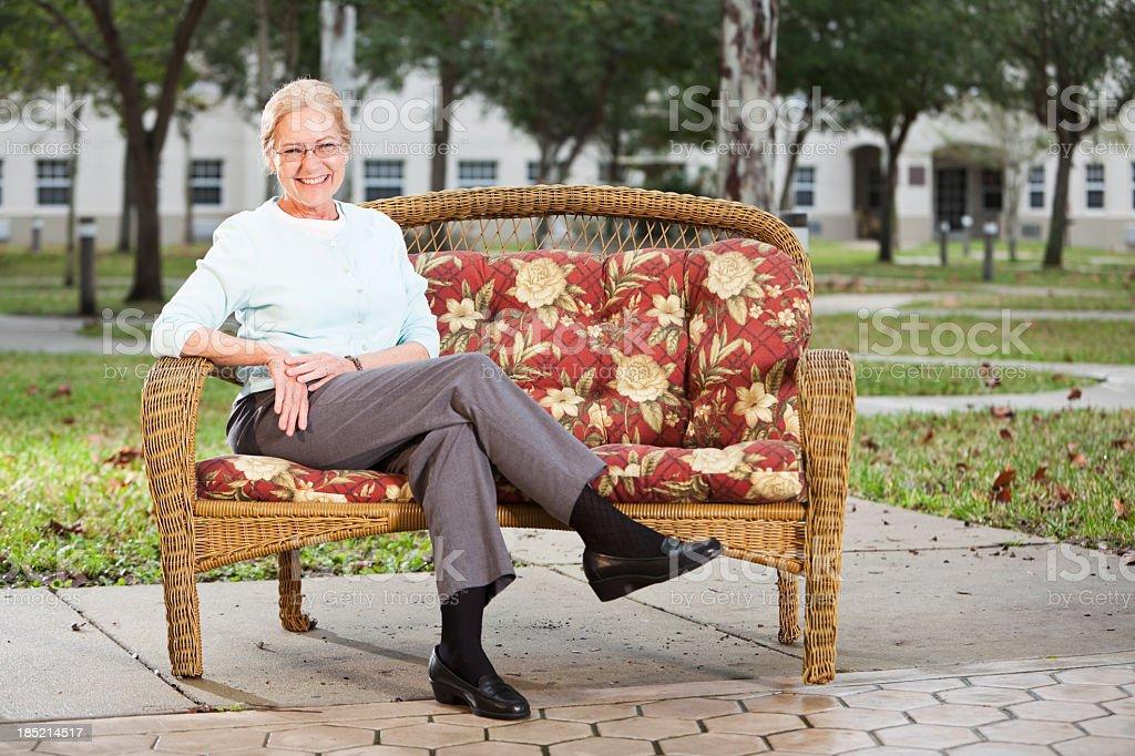 Senior woman on sofa outdoors stock photo