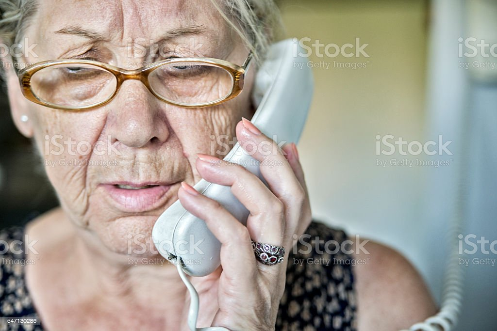 Senior woman on the phone with a look of  surprise stock photo