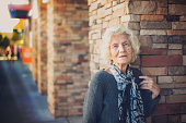 Senior Woman on the Street Leaning on Stone Wall