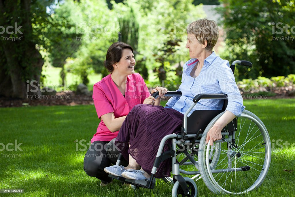 Senior woman on wheelchair with caring caregiver stock photo