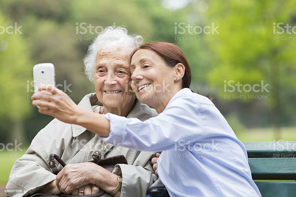 Senior woman on wheelchair with home caregiver in the park stock photo