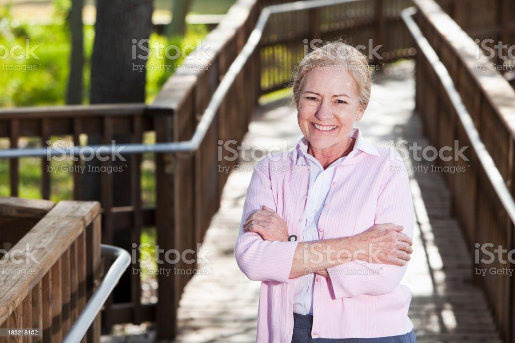 Senior woman on wooden walkway royalty-free stock photo