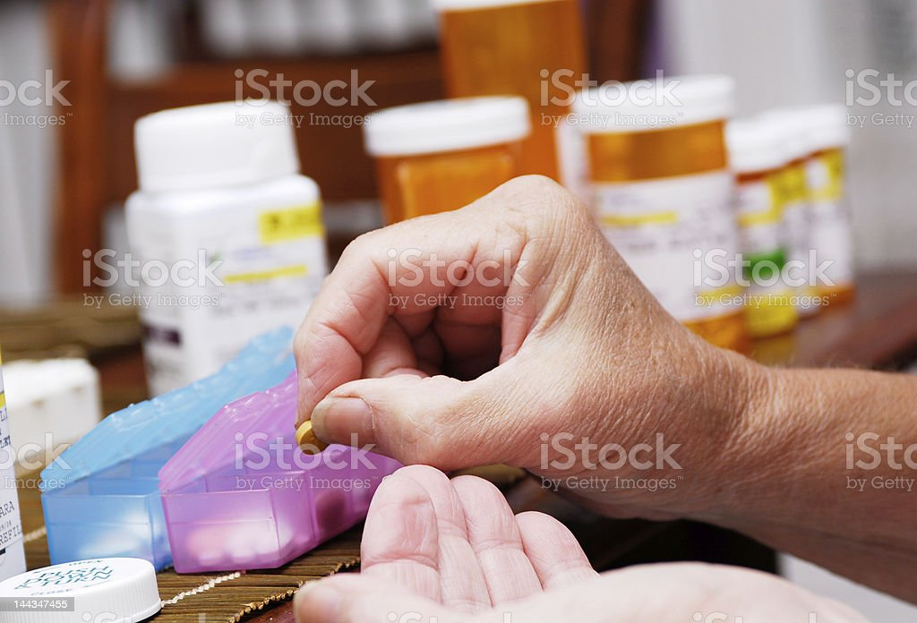 Senior Woman Organizing Pill Box stock photo