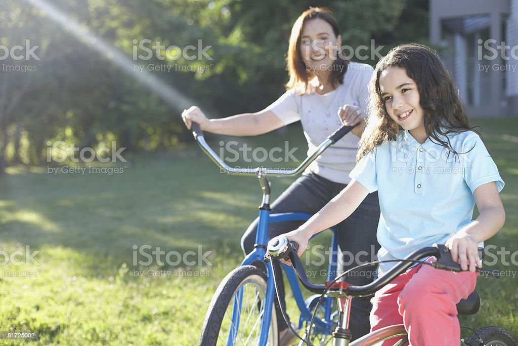 Senior woman outdoors with smiling young girl riding bicycles royalty-free stock photo
